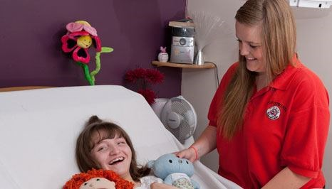 Young female carer stood next to a smiling girl in a hospital bed