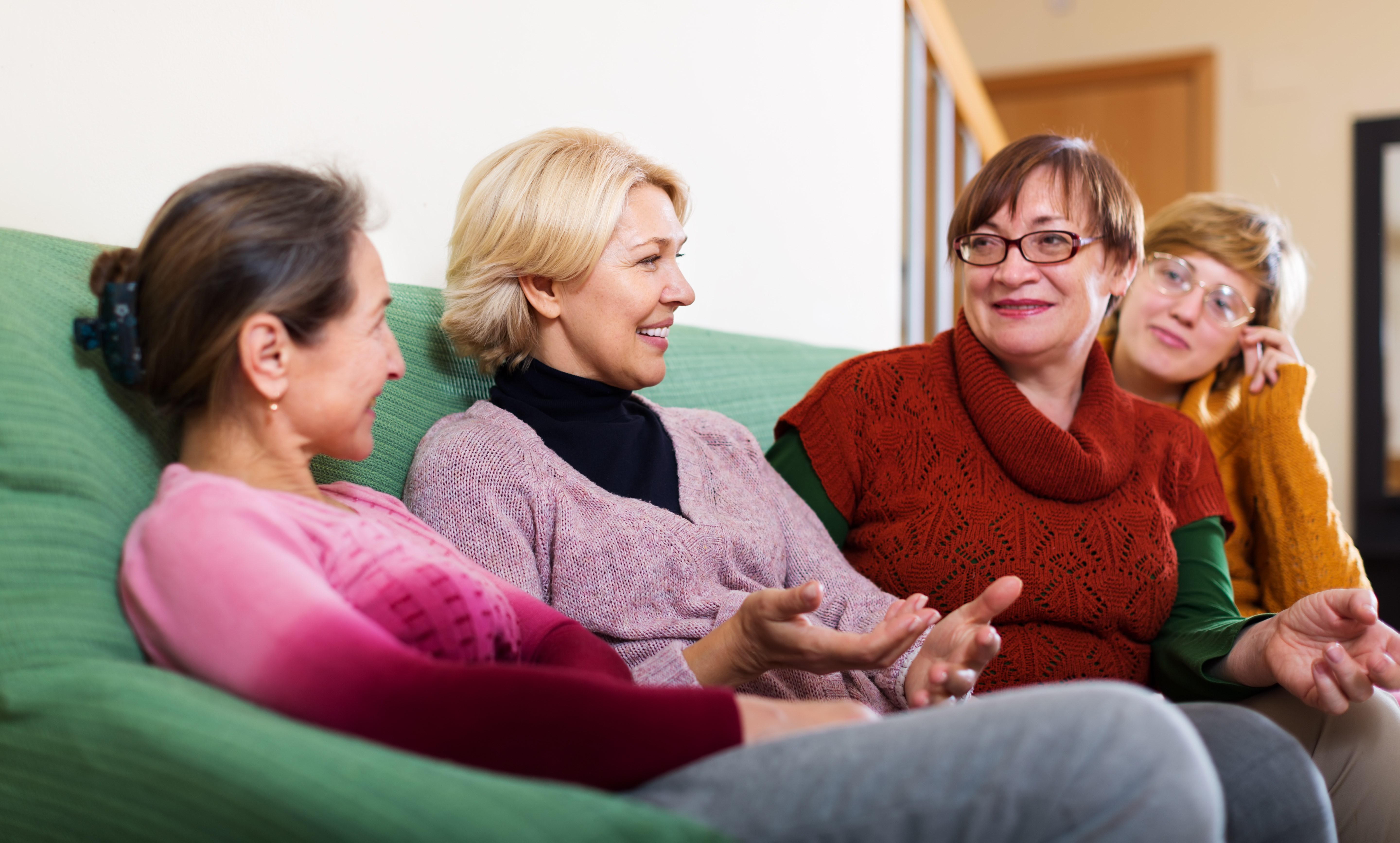 Four women chatting on a sofa