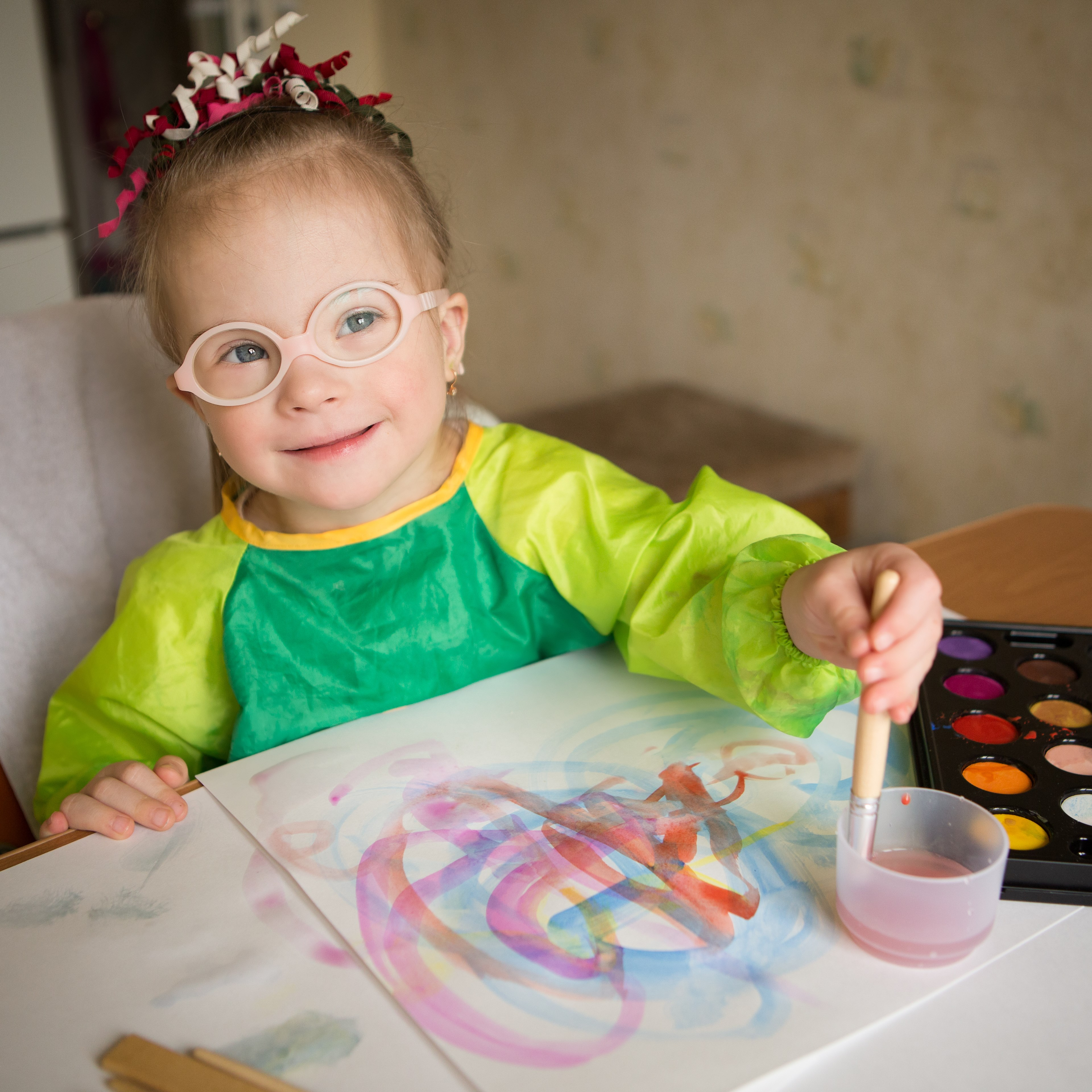 Young girl wearing glasses painting a picture at a table