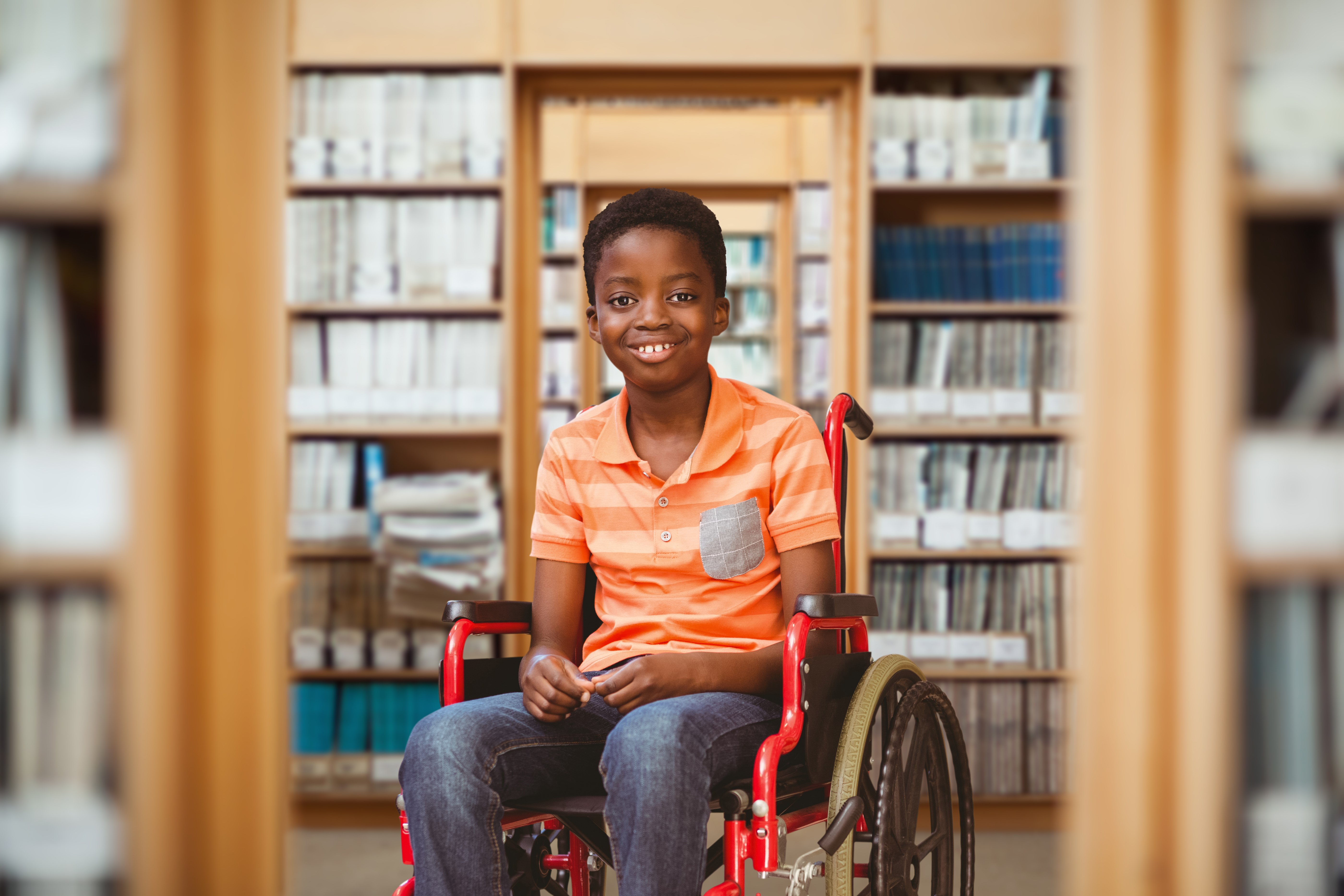 Young boy sitting in a wheel chair smiling at the camera