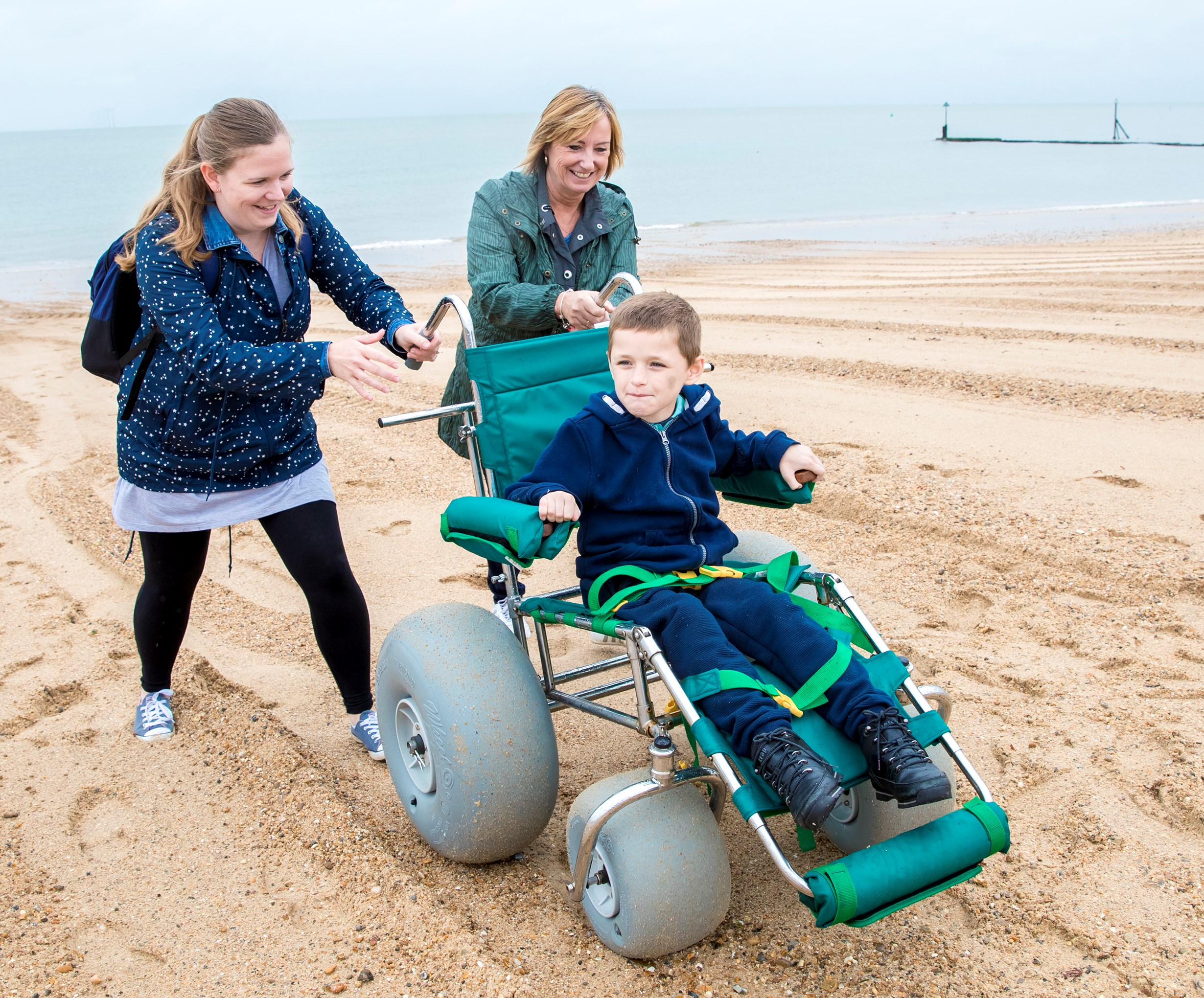 Two smiling women pushing a young boy in a wheelchair on a beach