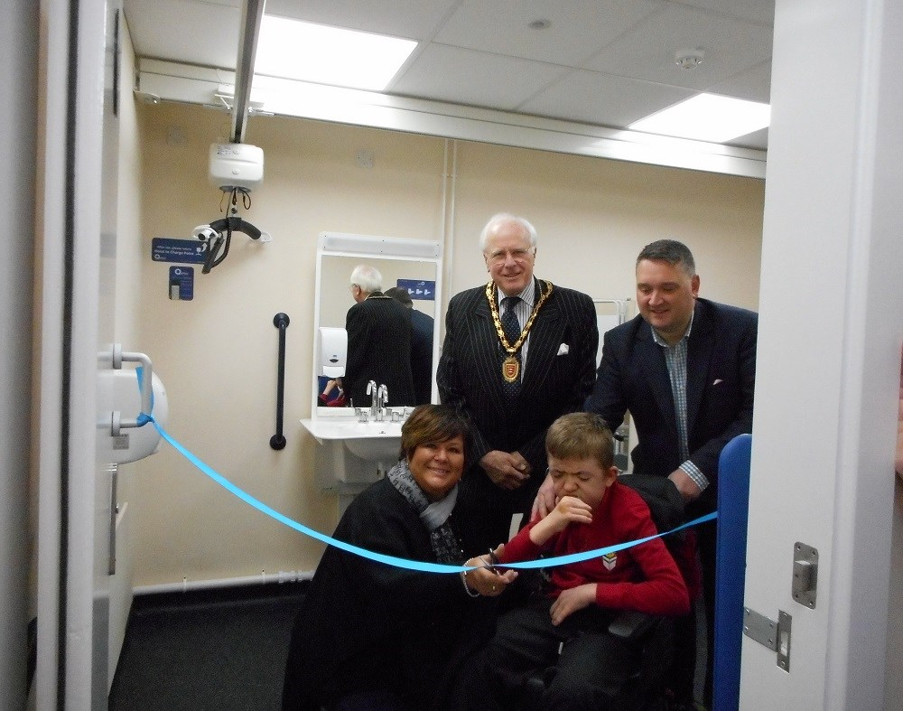 cutting the ribbon to open the changing places facility with people and mayor in the background